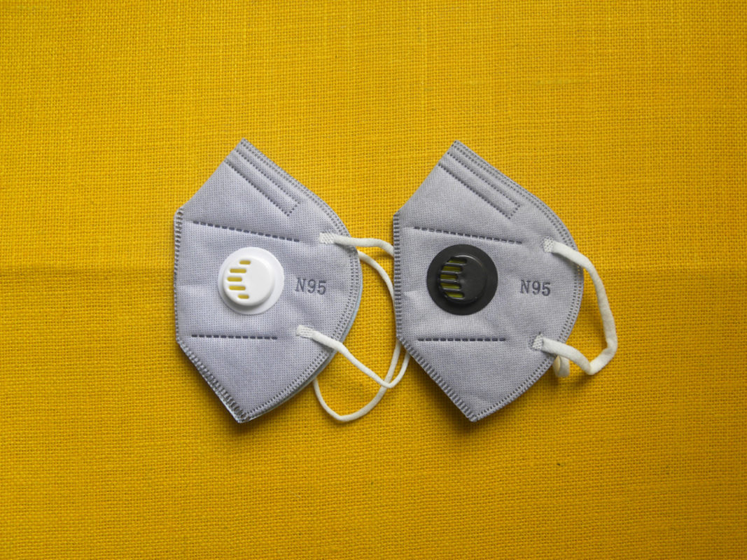 two gray fake n95 masks on yellow background