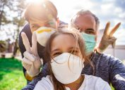 Two parents and their daughter wave at the camera while wearing face mask and latex gloves.