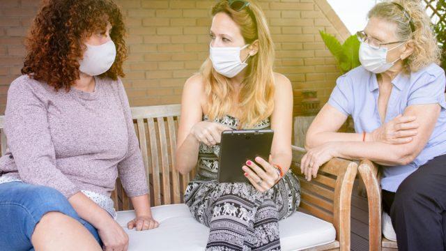 white women talking outdoors wearing coronavirus masks
