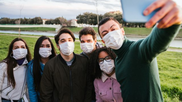 Group of teenage friends taking a selfie at park wearing protective masks