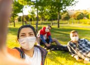 A group of young friends wearing face masks take a selfie in a park