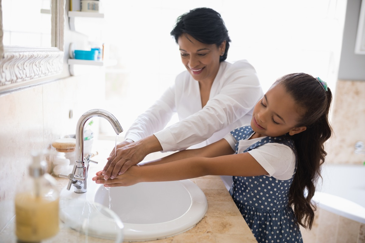 Mom helping her daughter wash her hands