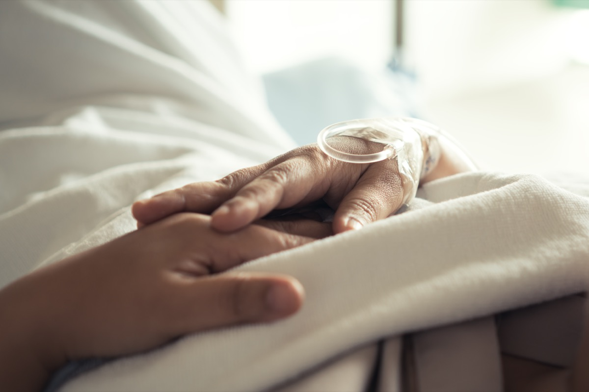 Holding hands on hospital bed sick with coronavirus