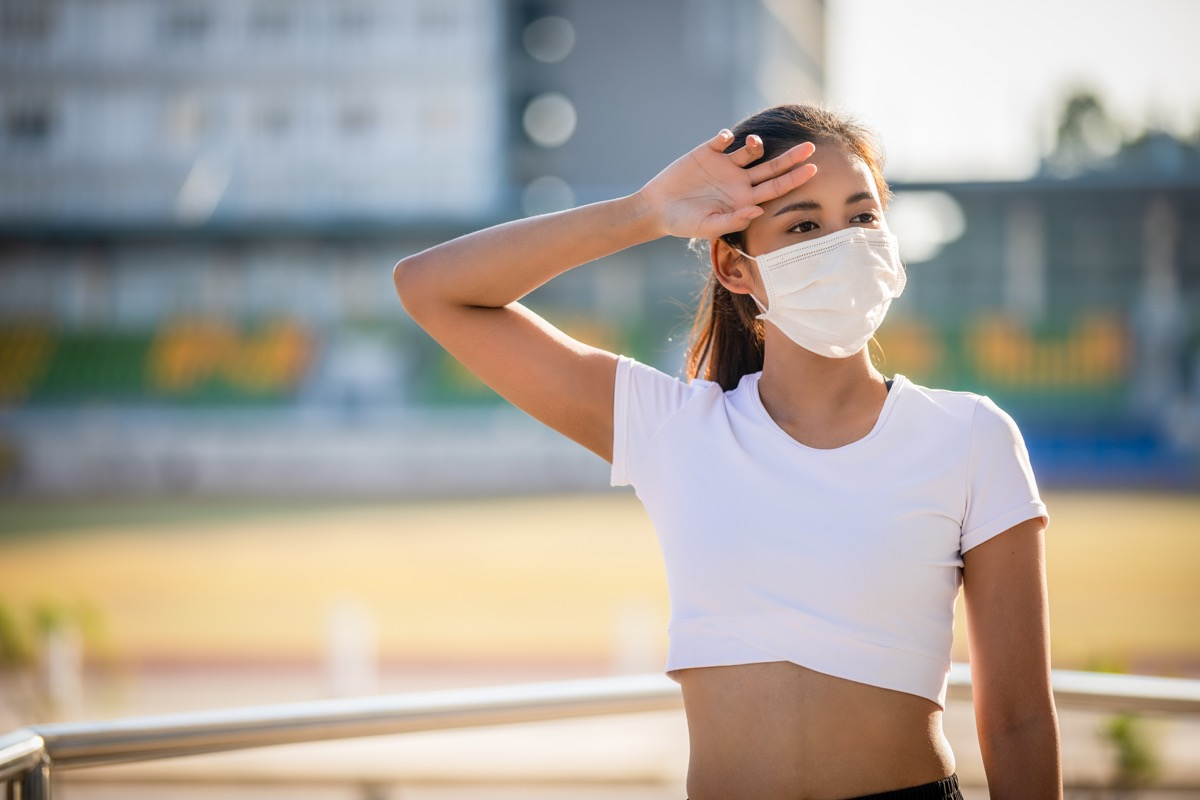 fitness sport woman is resting tired and she wears a mask for protective Dust and pollution on city
