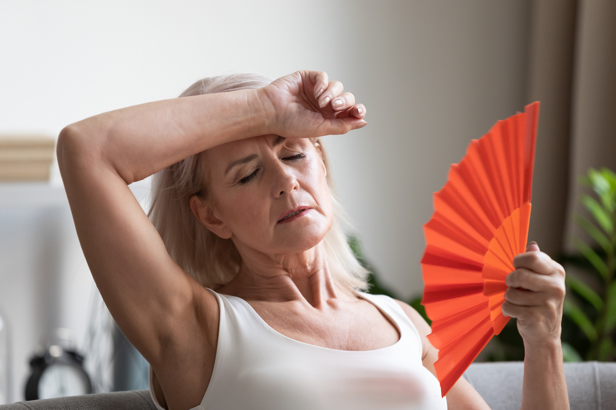 overheated senior woman waving fan due to heat while sitting on couch