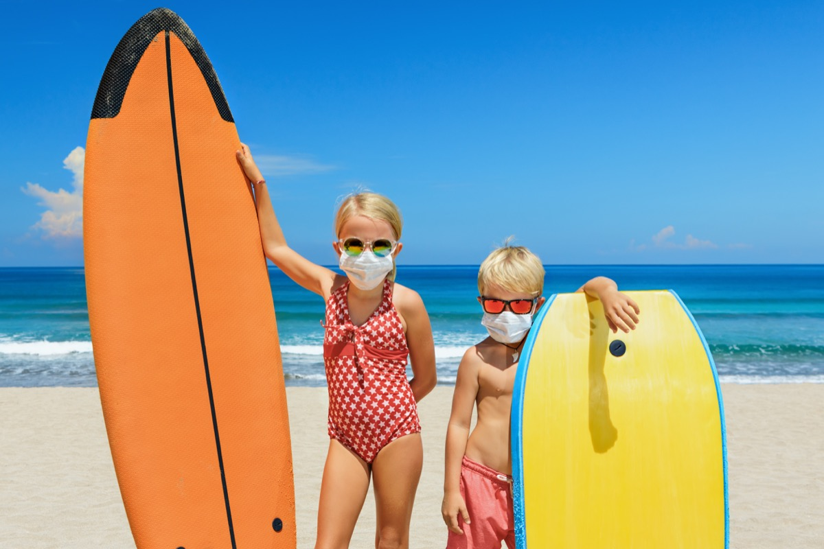 Kids wearing face masks on the beach to stay safe
