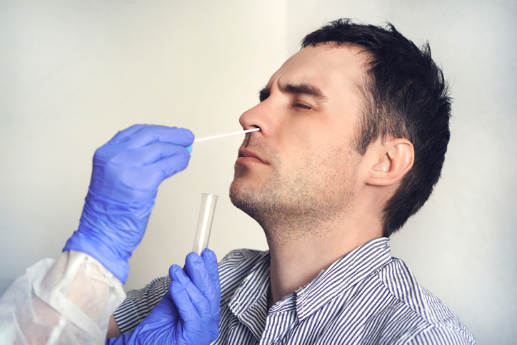A Caucasian man has his nose swabbed for a coronavirus test