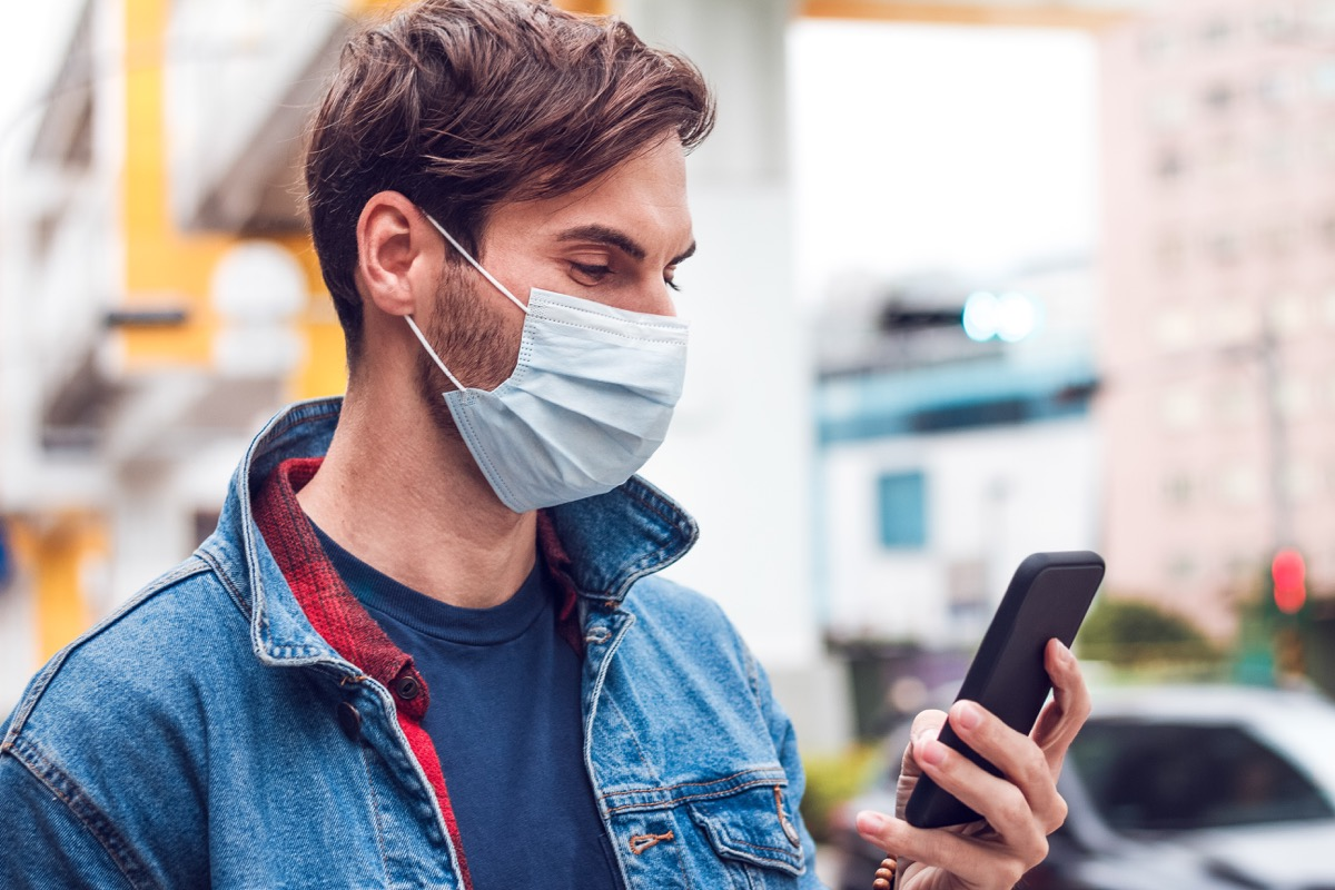 man with a mask looks at his phone
