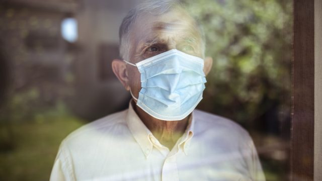 Senior man stays home because of Corona virus. He stands by the window and looks out at the garden.