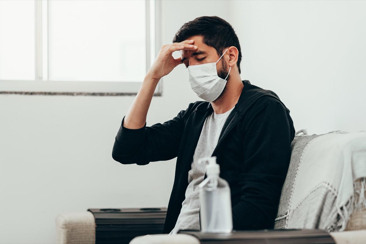 Sick man wearing mask with headache