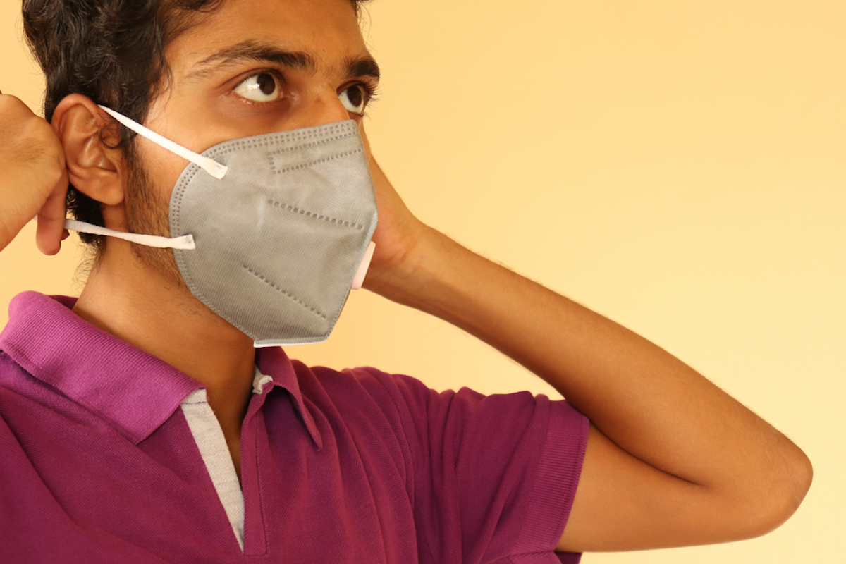young man putting on ear loops of mask