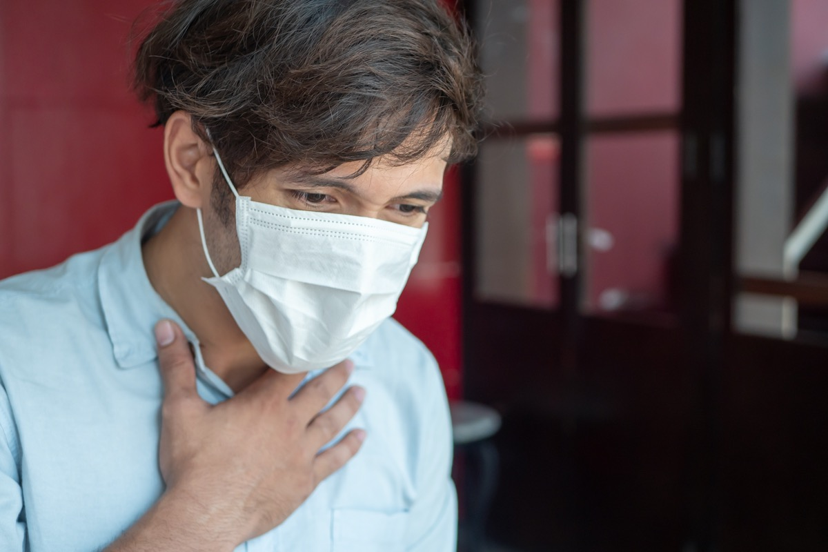 man in surgical mask grasping chest with breathing difficulties or asthma