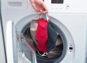 Hand putting cloth masks in washing machine