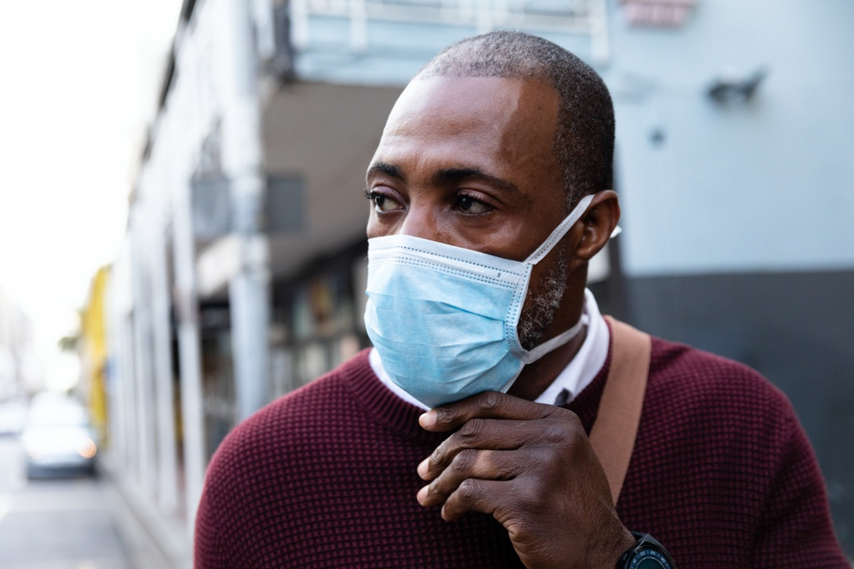 middle aged black man outside adjusting his surgical face mask amid the coronavirus pandemic