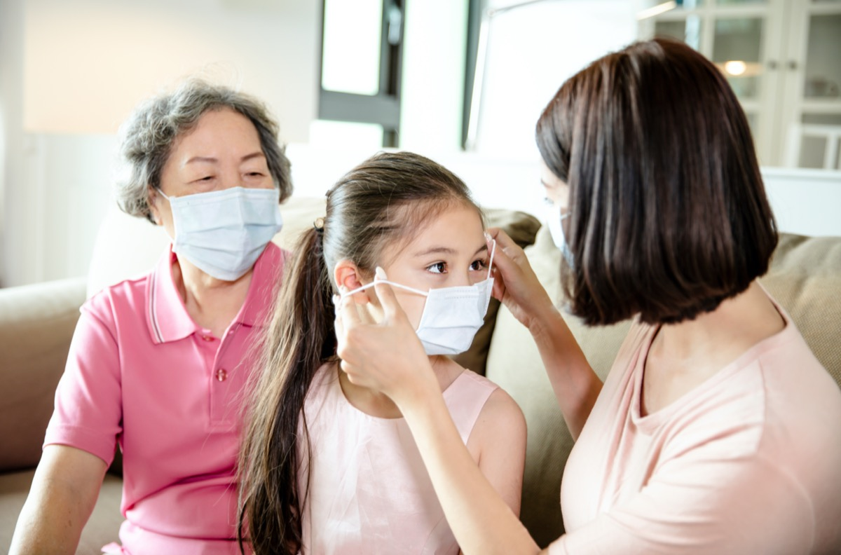 mother putting mask on young daughter