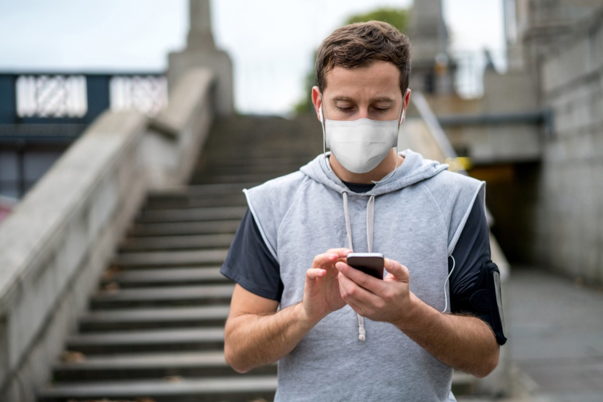 Portrait of a male jogger outdoors wearing a facemask and listening to music while working out in quarantine – COVID-19 lifestyle concepts