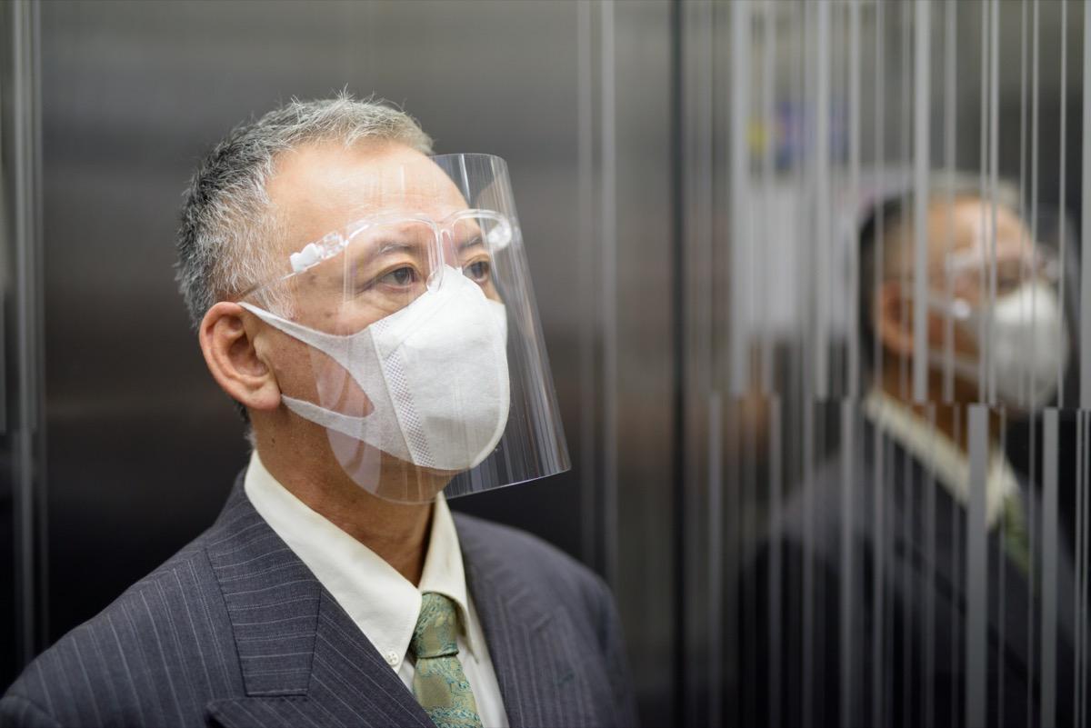 older asian businessman riding elevator while wearing face shield amid coronavirus