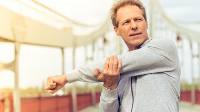 older white man stretching outdoors