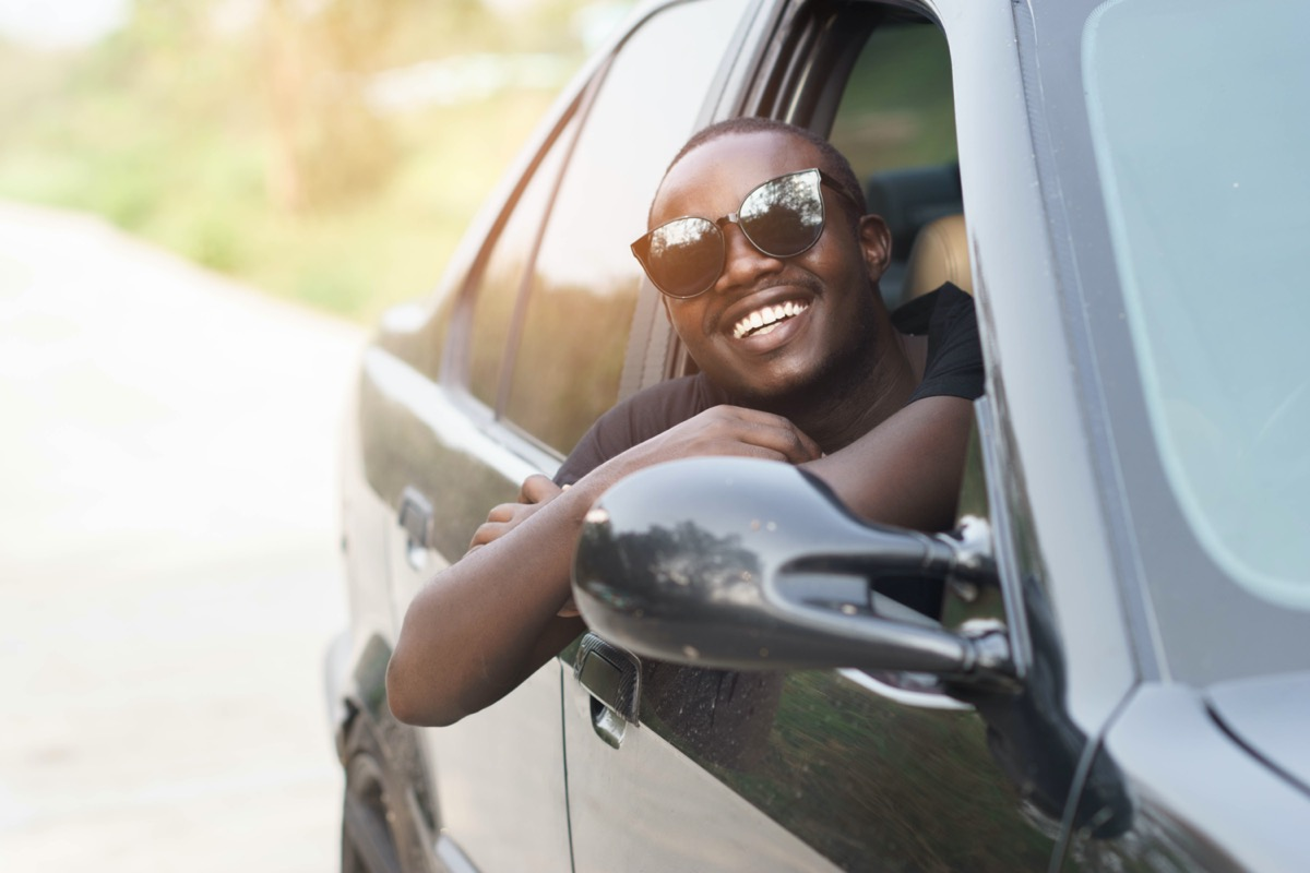 young black man in sunglasses leaning out open car window
