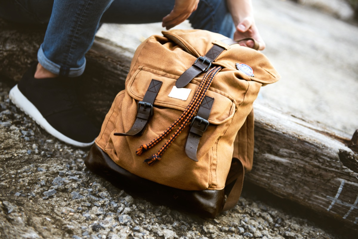 young white woman packing backpack