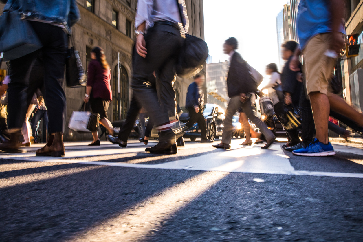 Pedestrians cross a busy crosswalk in the downtown area of a city.