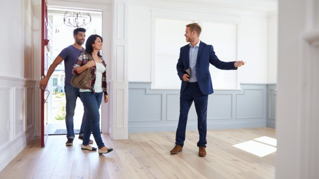 real estate agent showing home to young couple