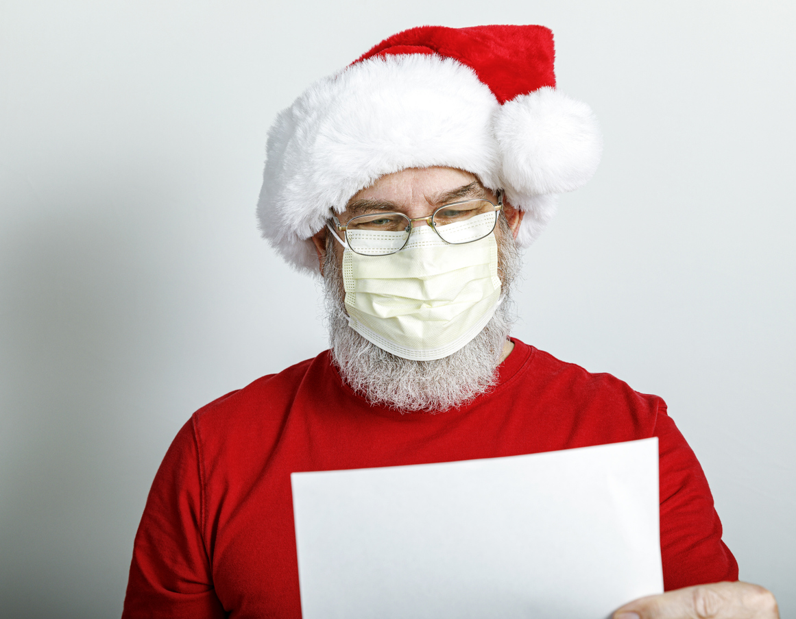 A Santa Claus character reads from a list while wearing a protective face mask