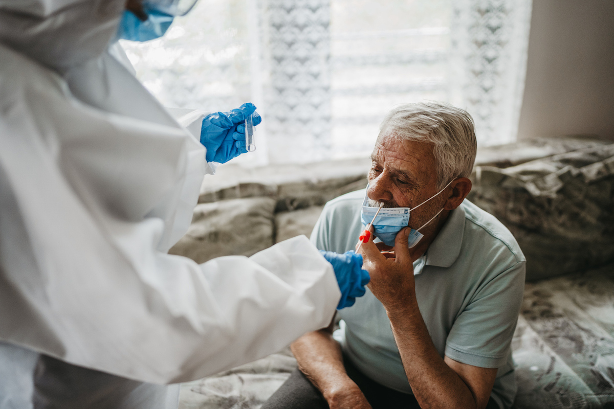 Female doctor in protective suit taking nasal swab test from a senior man