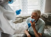 Doctor in protective suit taking nasal swab test from a senior man