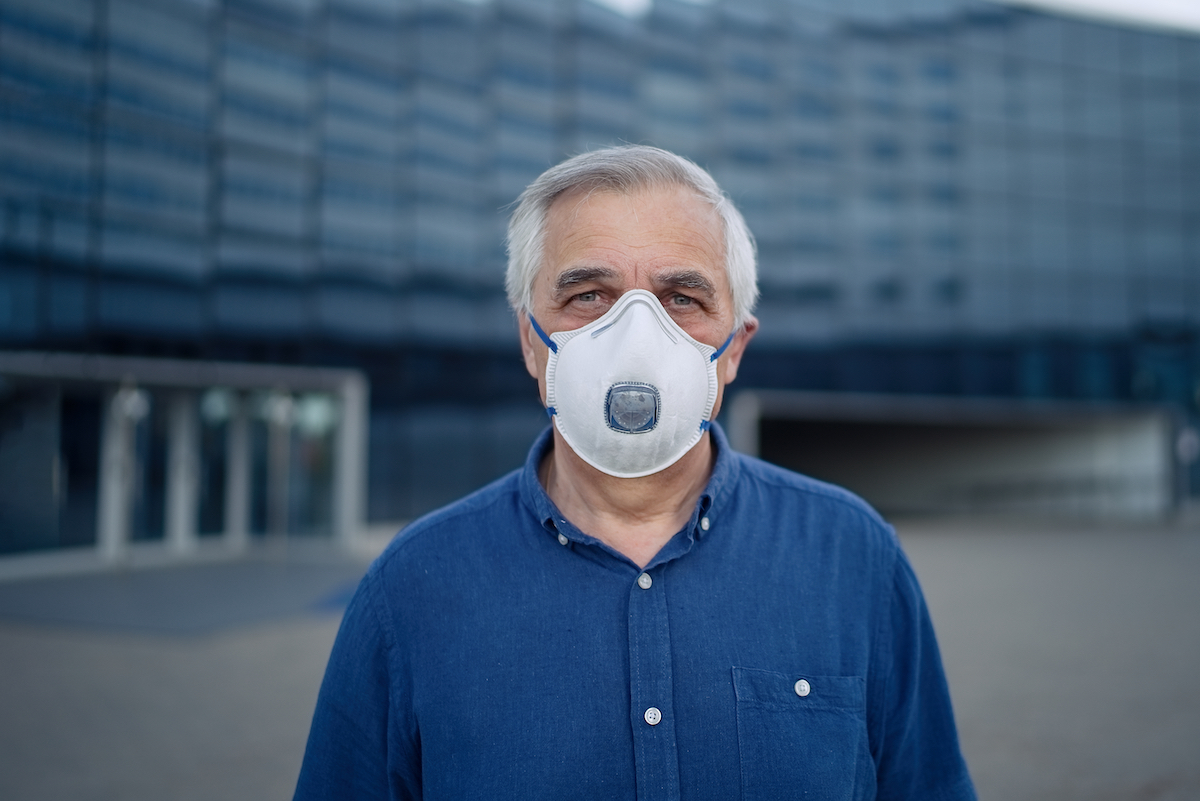 senior man wearing mask with respirator in front of office building