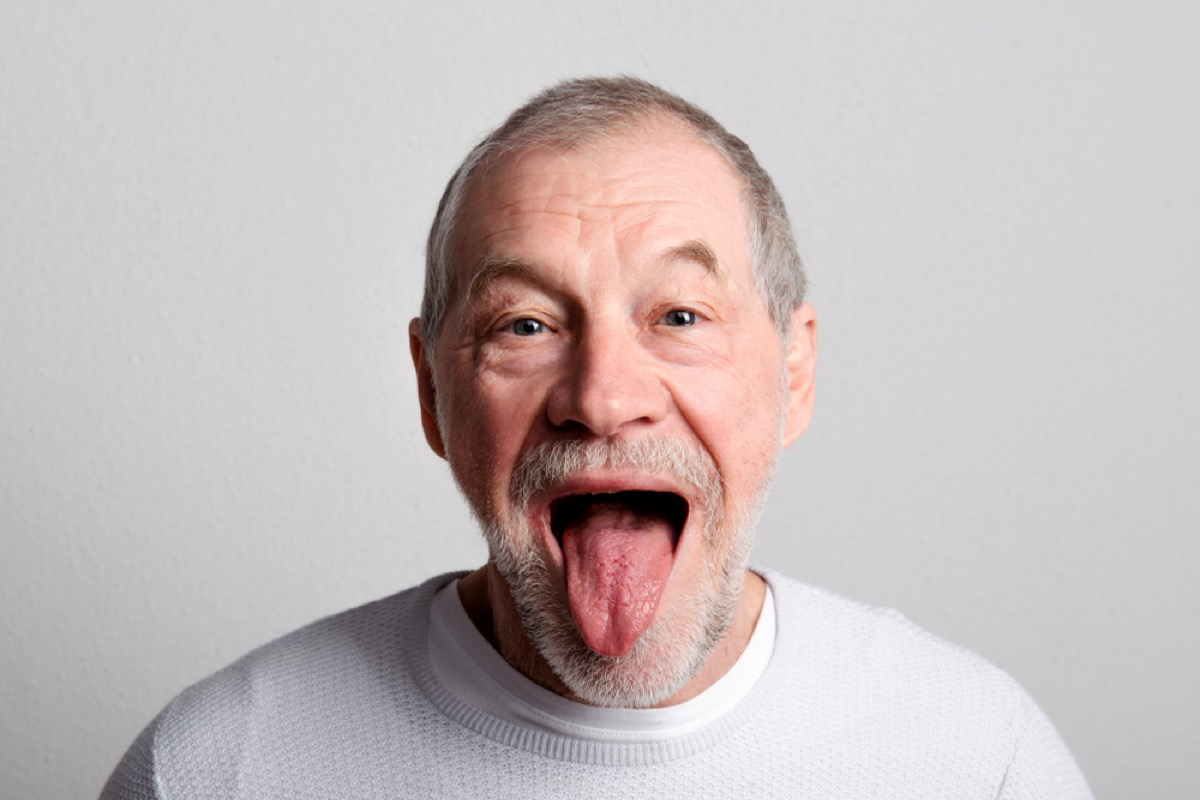 older white man looking at the camera and sticking his tongue out