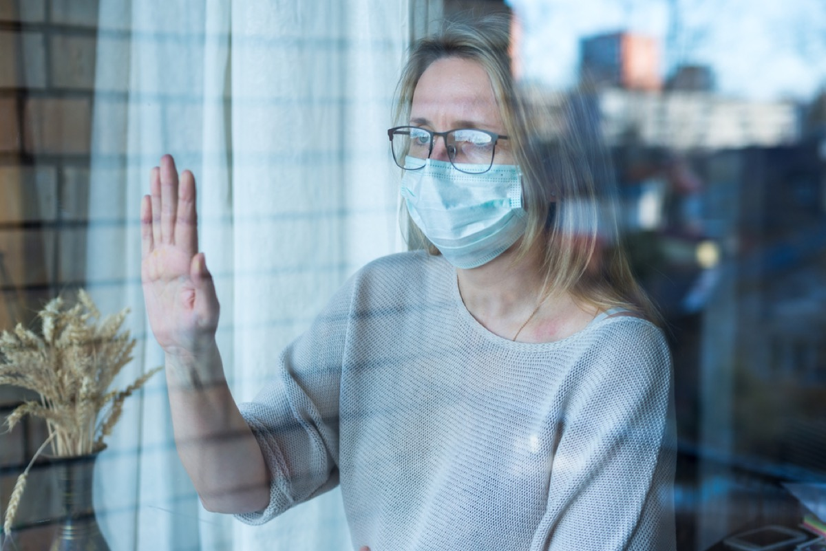 woman with face mask pressing her hand against the window