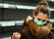 woman with mask coughing into her arm in front of empty shelf at supermarket