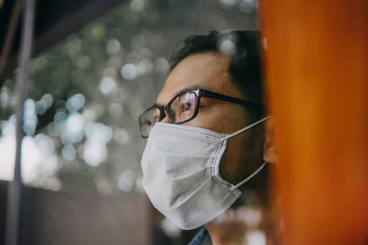 asian man with face mask looking out a window