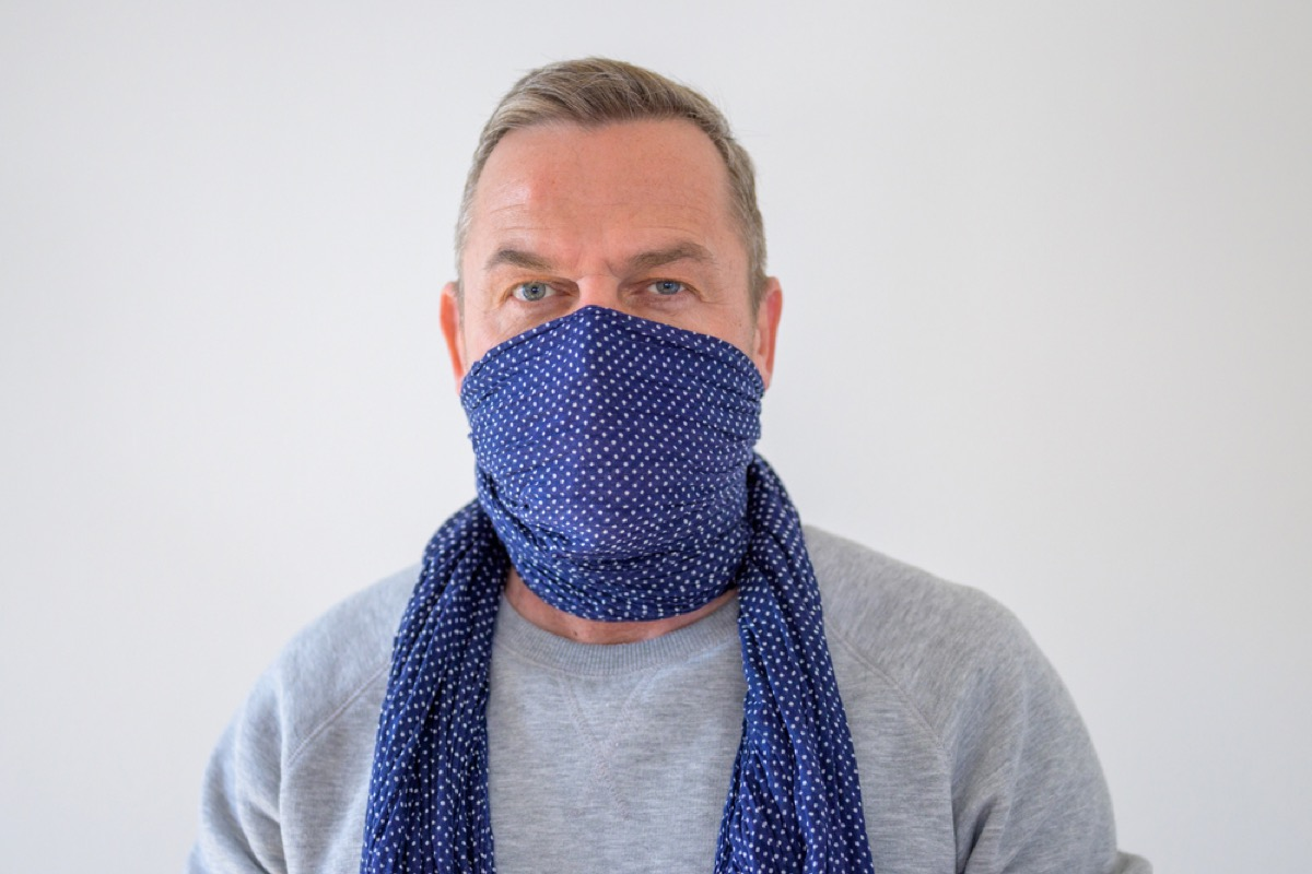 older white man wearing scarf as face covering