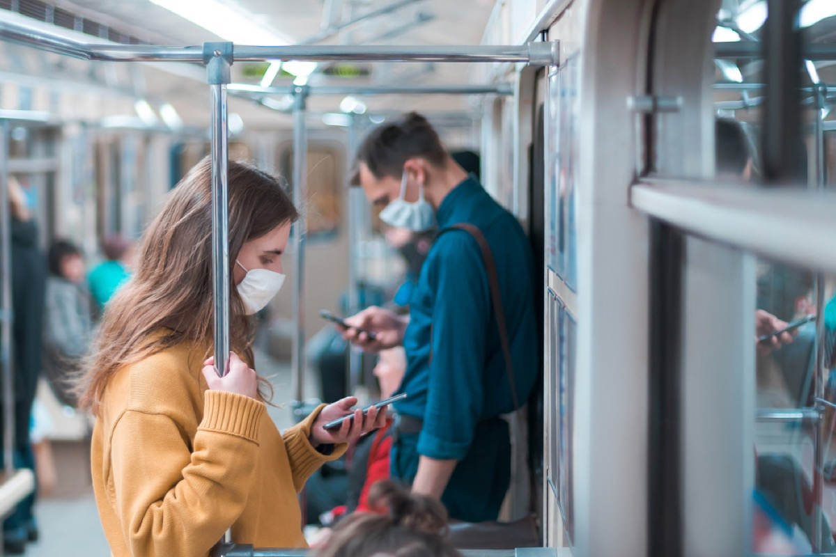 woman with face mask looking at her phone on subway with man in a face mask behind her