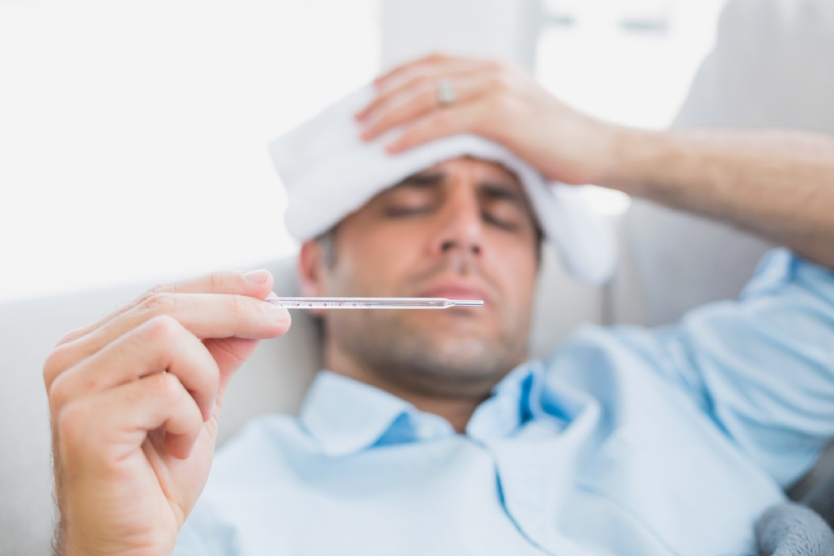 man on couch checking his temperature for fever