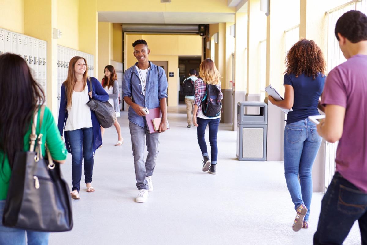 high school students walking down a school hallway