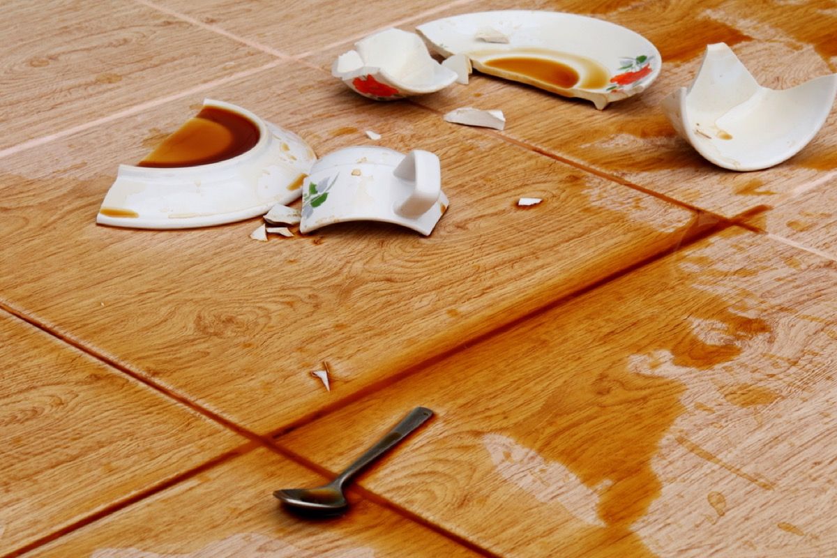 broken coffee cup and plate with spoon on the floor