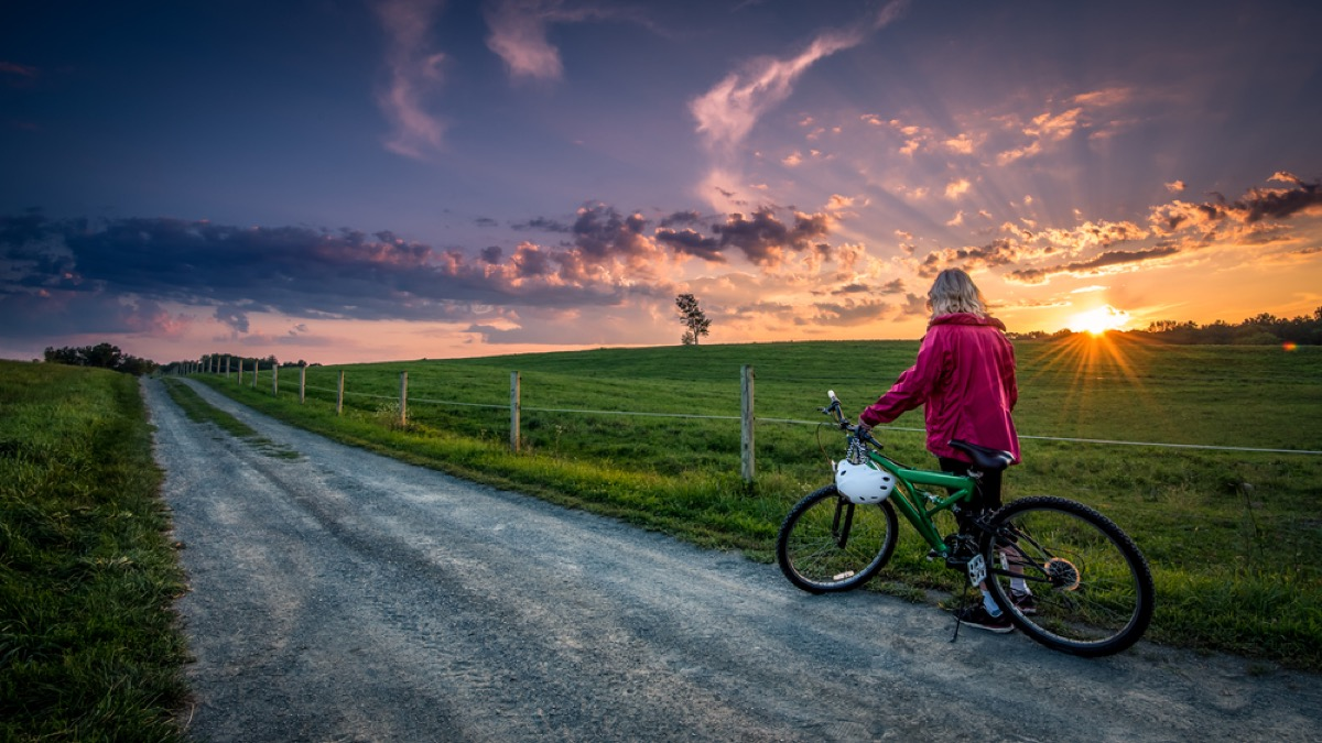 older woman with bike on a country road at sunrise