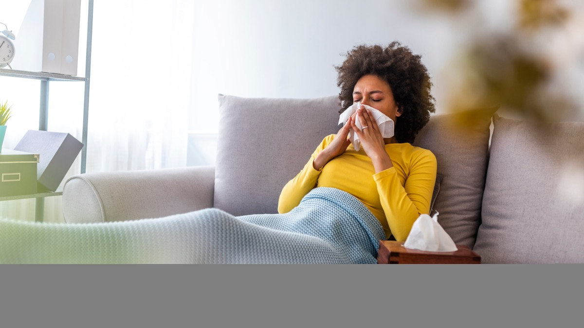 Woman on couch blowing nose sick at home