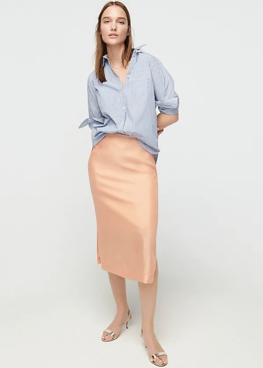 young white woman in orange silk midi skirt and blue top