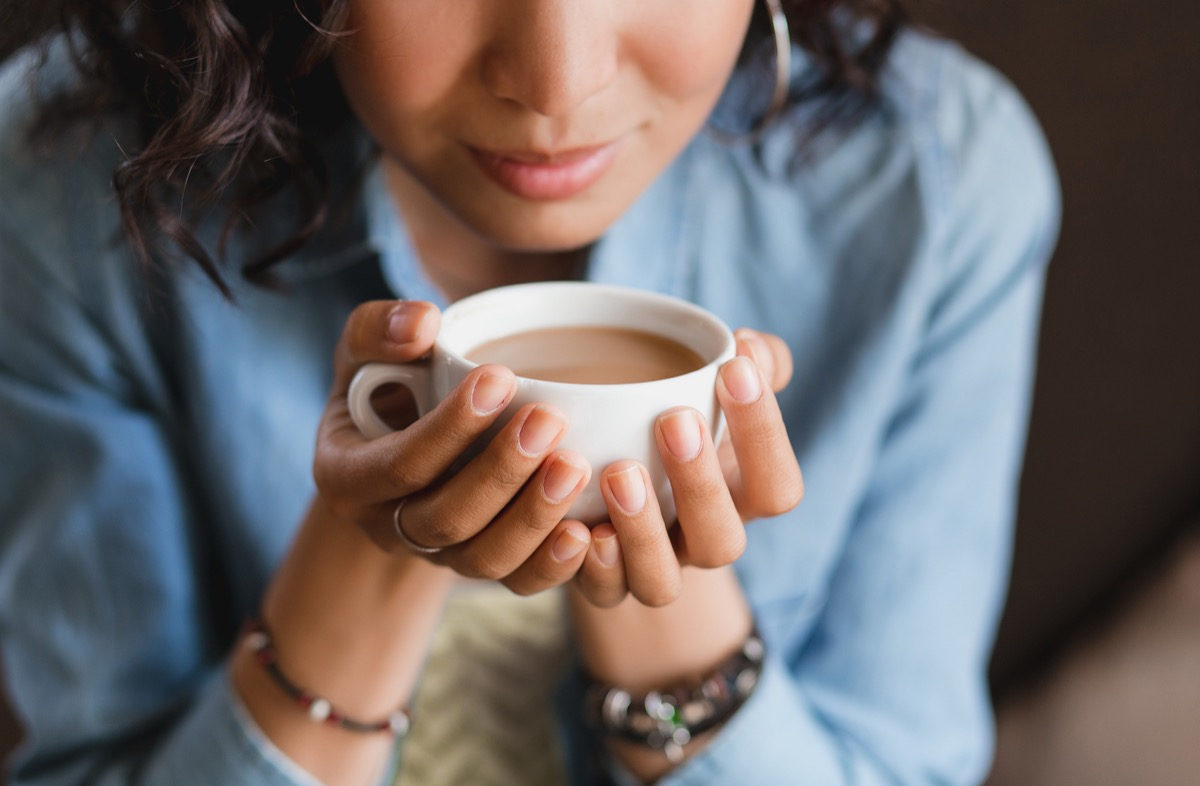 Woman trying to smell a cup of coffee
