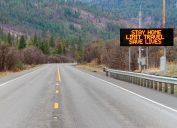 """An electronic sign on the highway warning citizens to """"stay home, limit travel, save lives"""""""