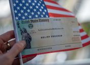 A hand holding a coronavirus stimulus check on top of an American flag