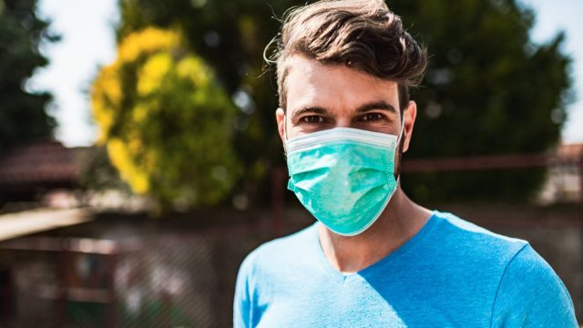 Man with pollution mask outside