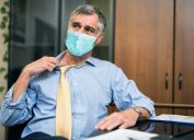 Man sweating because the temperature is hot at work while wearing a mask