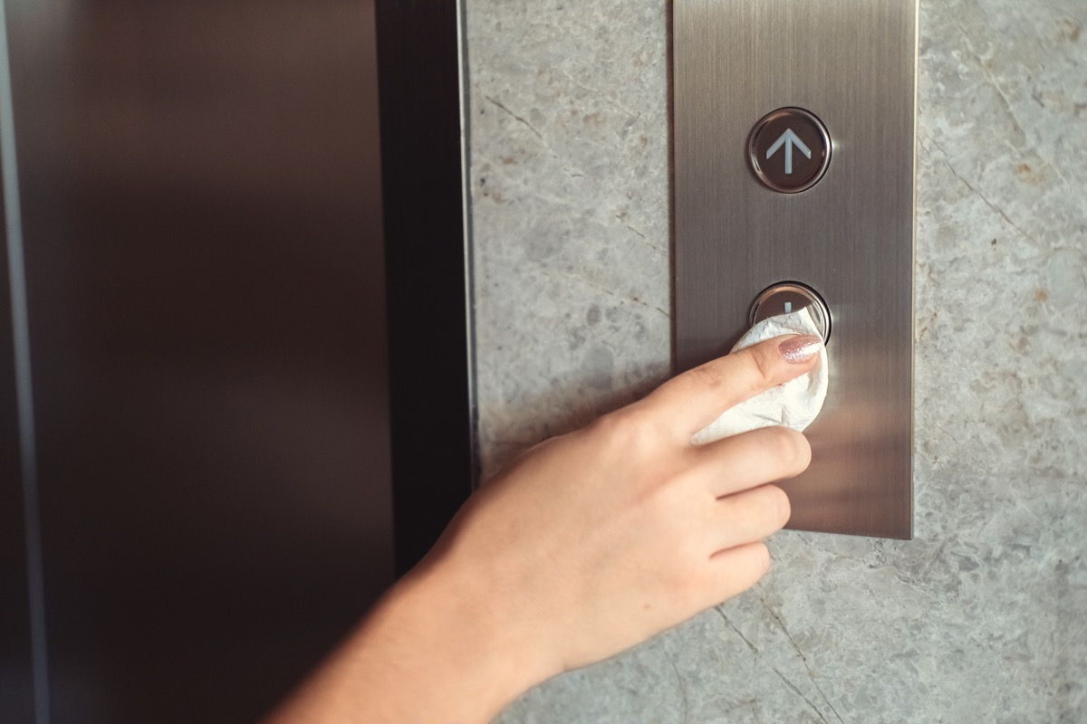 A hand is pressing elevator button through tissue paper. Infection prevention and control of Corona virus Covid-19 epidemic outbreak (A hand is pressing elevator button through tissue paper. Infection prevention and control of Corona virus Covid-19 ep