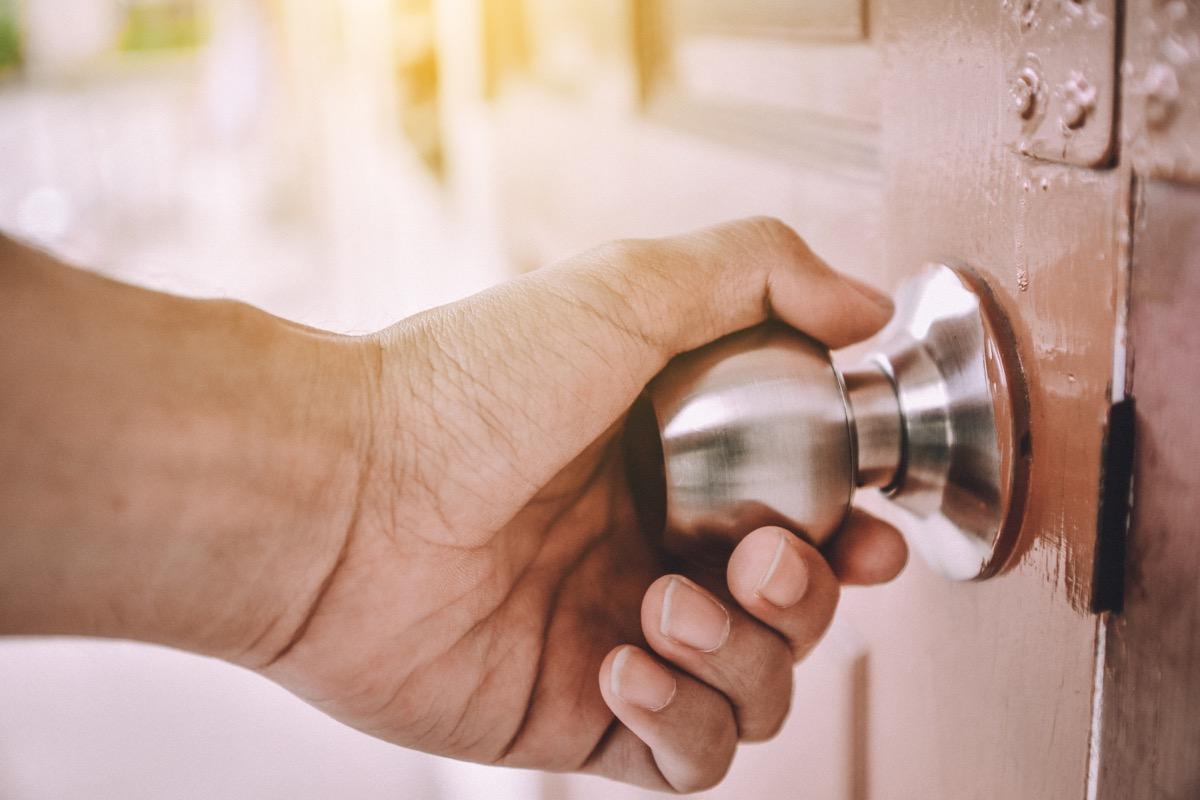 Hand opening the door in house