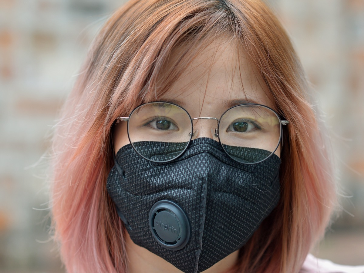Girl wearing a face mask with a valve in it